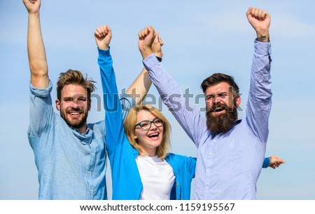 Company of three happy colleagues or partners celebrating success, sky background. Success concept. Men with beard in formal shirts and blonde in eyeglasses as successful team. Company reached top. #1159195567