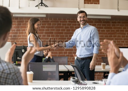 Company owner and newcomer shaking hands in office room. Young woman getting promotion feels happy and proud. Colleagues greeting new employee applauding. Advancement trust symbol and success concept