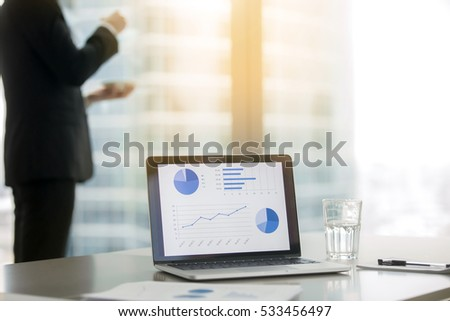 Company president in classical formal suit standing, looking at window and drinking coffee. Laptop with growing graphics on office table on foreground, focus on the screen. Business success concept
