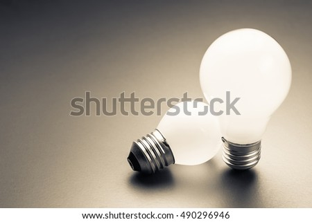 Comparative big and small light bulb, small and medium sized business, coaching, training, or other comparison concept #490296946