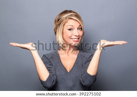 comparison concept - happy young blond woman displaying something on both flat hands for similar choice of product, gray background studio