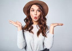 Comparison concept. Young brunette woman in casual clothes and brown hat displaying something on both flat hands for similar choice of product, gray background studio
