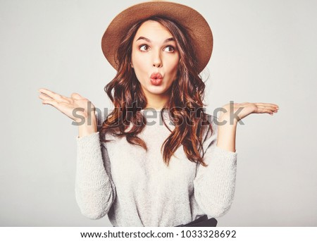 Comparison concept. Young brunette woman in casual clothes and brown hat displaying something on both flat hands for similar choice of product, gray background studio ストックフォト ©