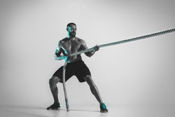 Comparison of forces. Young caucasian bodybuilder training over studio background in neon light. Muscular male model with the rope. Concept of sport, bodybuilding, healthy lifestyle, motion and action