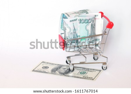 Comparison of national currencies - US dollars and Russian rubles next to the supermarket trolley. Depreciation and purchasing power of the currency. White background