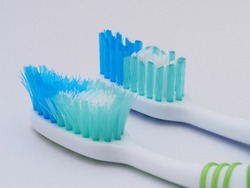 Comparison of the old and new toothbrushes in macro view, showing different bristle conditions: time to change a new toothbrush