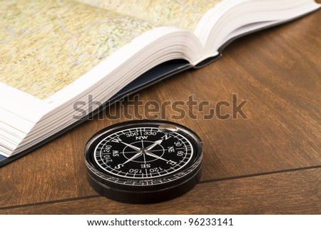 Compass and atlas book on the wooden table - stock photo