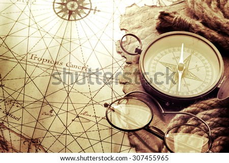 compass and glasses on antique...