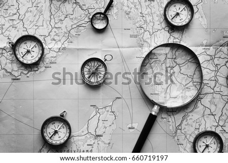 Compass and magnifier on a map #660719197