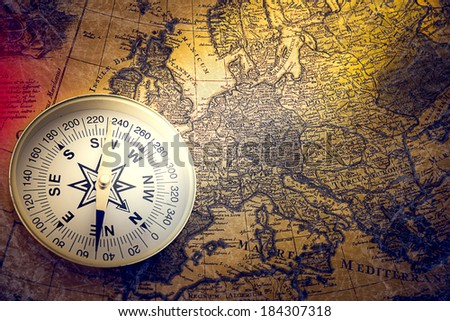 compass and magnifying glass gold color on the old map with coins