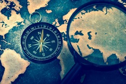 Compass and magnifying glasses on grunge world map