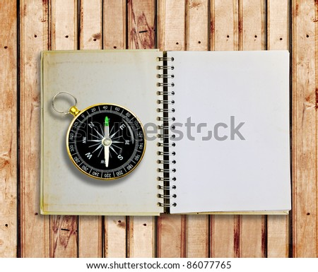 Compass and Old notebook on wood panels for background