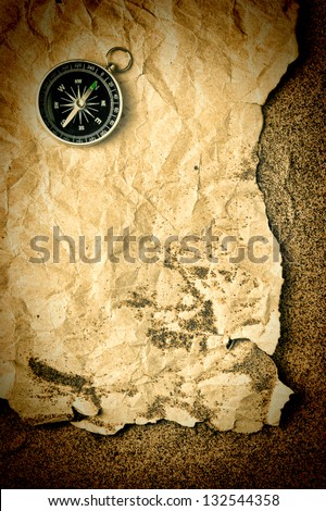 compass and old torn paper on a sandy beach