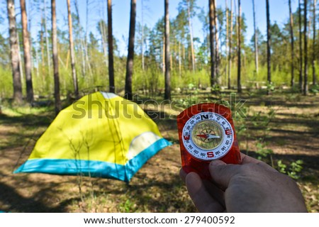 Compass and tourist tent. The magnetic compass in the hand against the tent in the forest in spring.