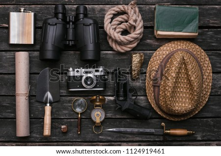 Compass, binoculars, film photo camera, loupe, dagger, handgun, diary book, shovel, rope, gold ore and old scroll document on adventurer or explorer wooden table. Traveler. #1124919461