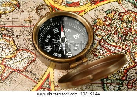 Compass closeup over 15th century world map