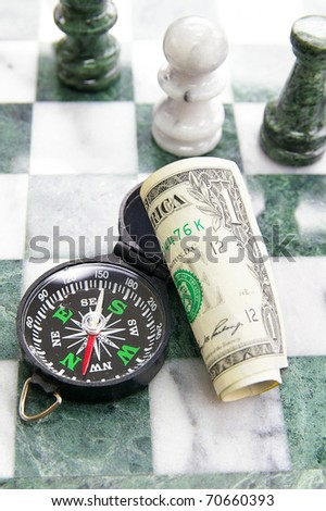 compass, dollar bill and chess pieces closeup