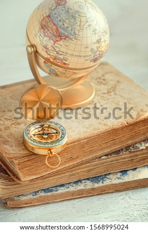 Compass, globe and books. travel and adventure background concept. soft selective focus. close up. shallow depth #1568995024