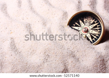Compass in sand. Shallow depth of field - focus on the compass