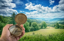 Compass in the hand against mountain. Travel geography navigation concept background.