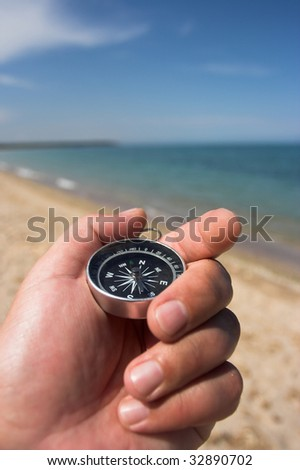compass in the hand,beach in the background