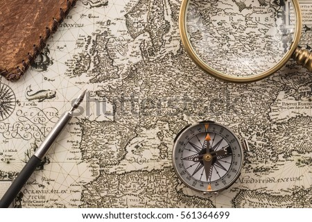 Compass, ink pen, magnifier and folder on vintage map