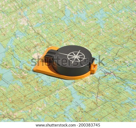Compass lies on a topographic map. Compass on the map - this is the open door to the country adventure.