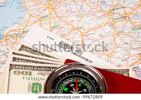 compass, money and passport with boarding pass