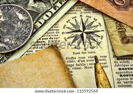 Compass, old documents and money on paper