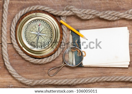 Compass, old notebook, pencil, magnifying glass, rope on wood