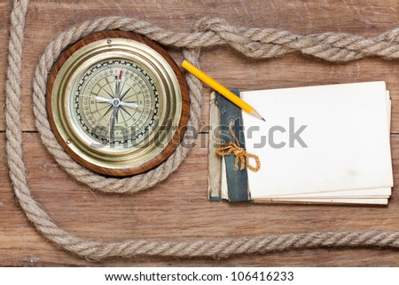 Compass, old notebook, pencil, rope on wood