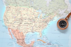 Compass on a map pointing at United States and planning a travel destination