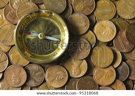 Compass on a pile of American pennies representing finance and economy directions.