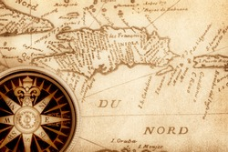 Compass on old handwritten map of Haiti