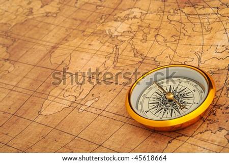Compass on old map. Gold comapss and yellow map