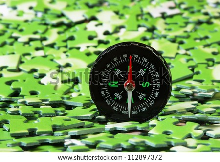 compass on pile of green puzzle