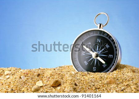 Compass on sea sand and a dark blue background