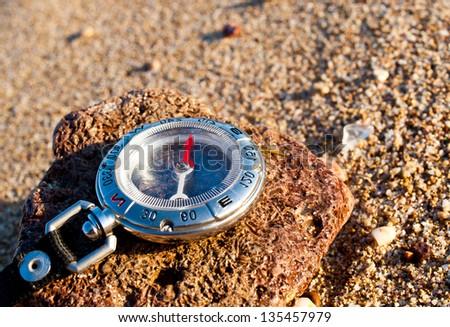 Compass on the beach. Tourist equipment
