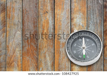 Compass on the old wooden board surface