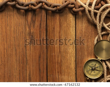 Compass, rope and chain on wooden board - stock photo