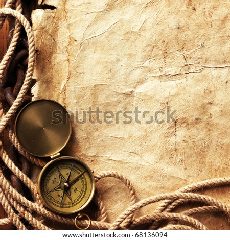 Compass, rope, paper, chain on wooden board