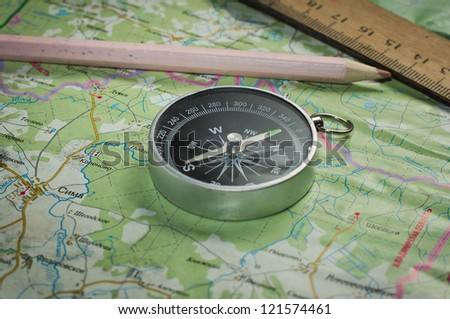 Compass, ruler and pencil on a map