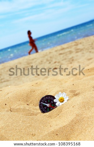 compass with flower on beach