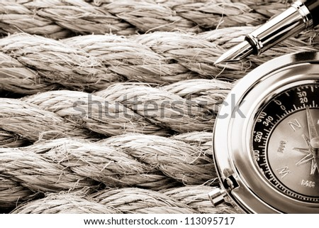 compass with ink pen on ship ropes
