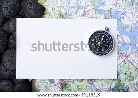 Compass with rock cover water and map