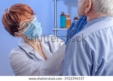 Compassionate female doctor in white coat and mask put her gloved hands on the neck of senior male patient. Professional medical care in the hospital. Photo stock ©