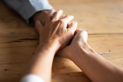 Compassionate middle aged wife covering wrinkled hand of retired husband, overcoming grief together. Elderly woman giving psychological support to mature man or having sincere conversation indoors.