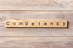 Competency word written on wood block. Competency text on table, concept.