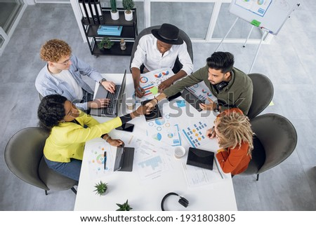 Competent IT specialists in stylish outfit working on modern gadgets while sitting together at bright office. Young multiracial people shaking hands, talking and smiling during cooperation.