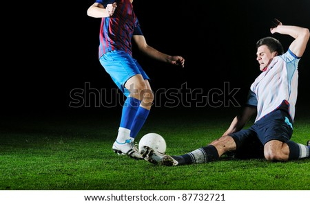 competition Action run and jump Duel of football players at soccer ball stadium at night - stock photo